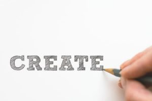"Graphic designer sketching out pencil typography spelling ""create""."
