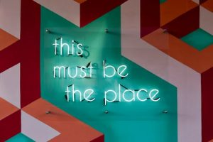 "Wall feature with neon lights reading ""this must be the place"" created by graphic designer."